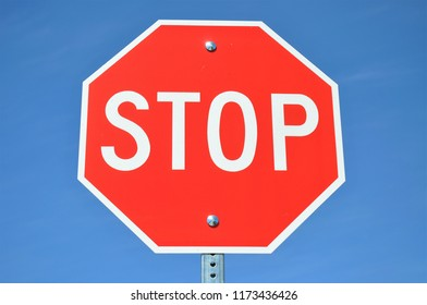 Stop sign against a bright blue sky.