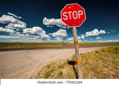 Stop sign with with bullet holes on empty open highway in Wyoming, USA