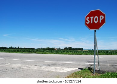 Stop sign in a country road on blue sky