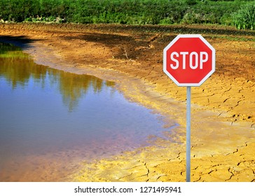 Stop sign in dry landscape caused by climate change with dry earth and drying lake