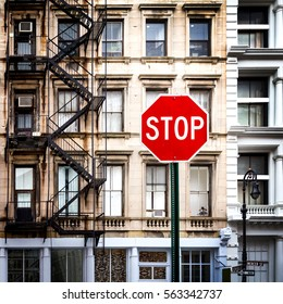 Stop sign in front of historic old buildings with windows and fire escape at the intersection of Howard and Mercer Streets in Lower Manhattan, New York City NYC