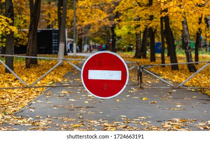 Stop sign at the gate for entering the park with autumn trees and fallen bright yellow leaves on the background of blurry people in the distance