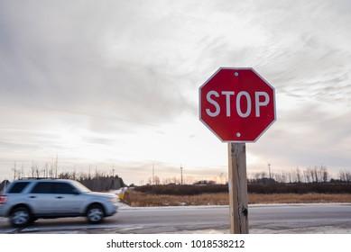 Stop Sign at an Intersection at Sunset with a Passing Car in Background