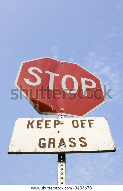 Stop sign and keep off grass sign against a blue sky. Heavy wear and dents on the signs.