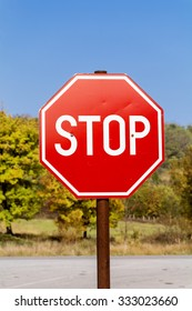 Stop sign on an autumn trees background