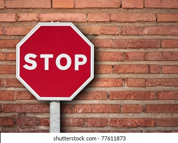 stop sign on a brick wall