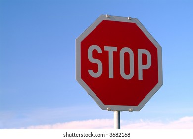 a stop sign on the road with a blue sky