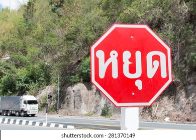 Stop sign on road in Thai languages.