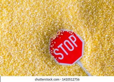 Stop sign on texture of Polenta, yellow Cornmeal flour, Semolina, fast cooking closeup of grains