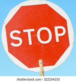 Stop sign on wooden stick - held by road construction workers to control traffic