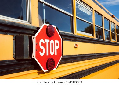 Stop sign with red lights on the side of the school bus
