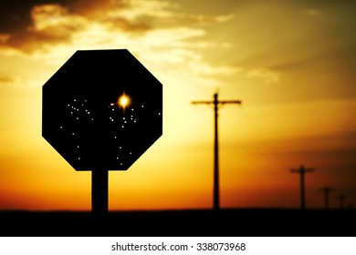 Stop sign that has been riddled with bullet holes against a brilliant morning sun.