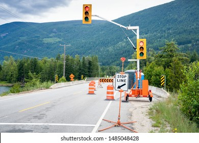 Stop sign and traffic lights at the beginning of a construction site along a mountain road. Traffic cones and barriers narrow the road to a one lane.