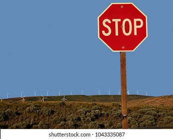 Stop! Sign with wind power towers in the background