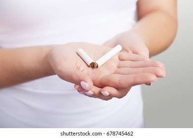 Stop smoking. A cigarette is broken in the palm of a young woman. Macro photography. The concept of health. On a gray background.