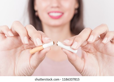 Stop smoking cigarettes concept. Portrait of beautiful smiling girl holding broken cigarette in hands. Happy female quitting smoking cigarettes. Quit bad habit, health care concept. No smoking.