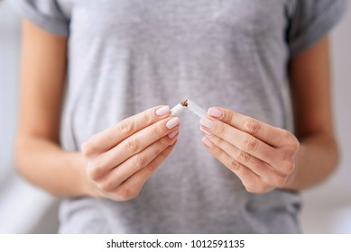 Stop smoking cigarettes concept. Woman holding broken cigarette in hands. Happy female quitting smoking cigarettes. Quit bad habit, health care concept. No smoking.