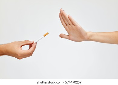 Stop Smoking Concept. Closeup Of Woman Hand Refusing To Take Cigarette. Human Hand Holding Cigarette On White Background. Quit Smoking Concept. High Resolution