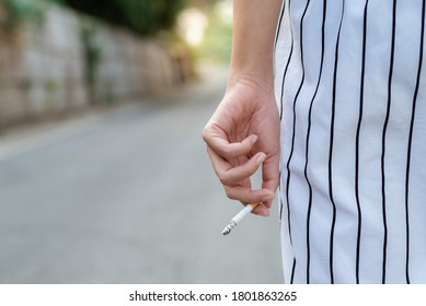 Stop smoking and Quit smoking cigarettes concept. Portrait of beautiful  girl holding broken cigarette in hands. Happy female quitting smoking cigarettes. Quit bad habit, health care concept.