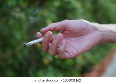 Stop smoking and Quit smoking cigarettes concept. Handsomeman holding broken cigarette in hands. Quit bad habit, health care concept.