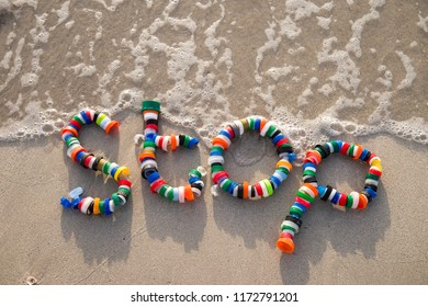 'STOP' spelled out on the sand using plastic bottle caps collected on Miami beach a as a message for people to take action on pollution