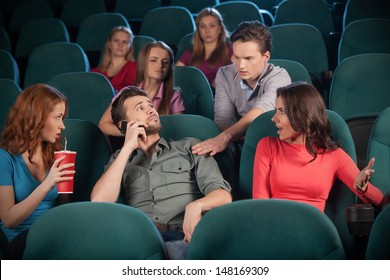 Stop talking! Young men talking at phone while watching movie at the cinema