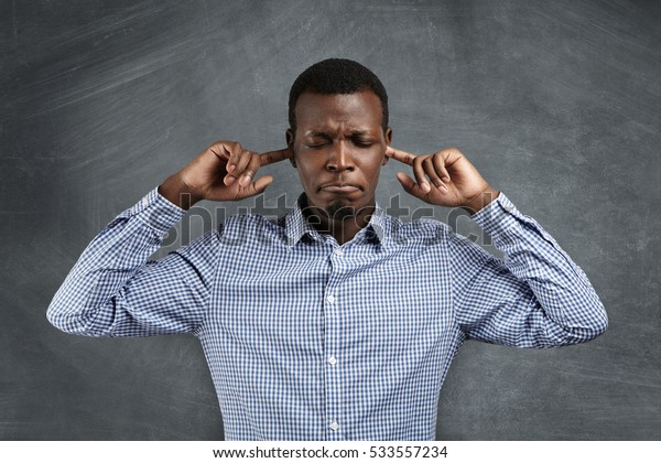 Stop this sound! Portrait of angry and frustrated African man in shirt stopping his ears, plugging them with fingers, closing eyes and pursing lips while suffering from loud noise. Negative emotions
