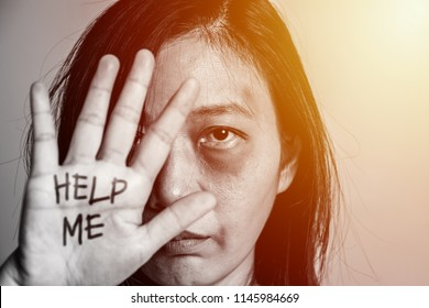 stop violence against women campaign. Asia woman with bruise on arms and face raised her hand for dissuade, hand write the word help me.