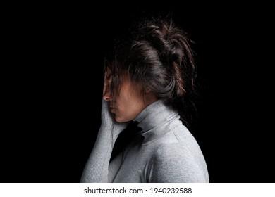 Konzept der Bekämpfung von Gewalt gegen Frauen: Seitenansicht einer unglücklichen Frau, die ihr Gesicht auf schwarzem Hintergrund hält. 8. März Frauentag oder Frauenrechtskonzept.