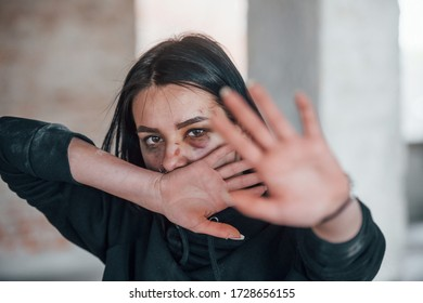 Stop the violence. Portrait of beaten young woman with bruise under eye indoors in abandoned building.