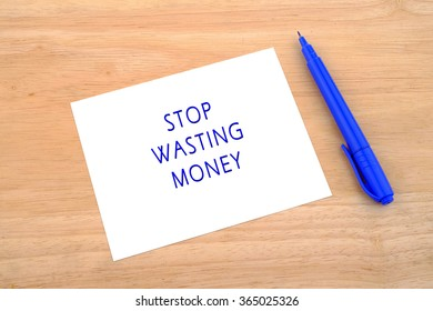 Stop Wasting Money written on paper over wooden background.