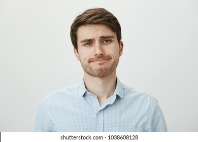 Stop wasting my time. Attractive caucasian bearded male in ordinary clothes making bothered face, being indifferent and listening without lack of interest or with disbelief standing over gray wall