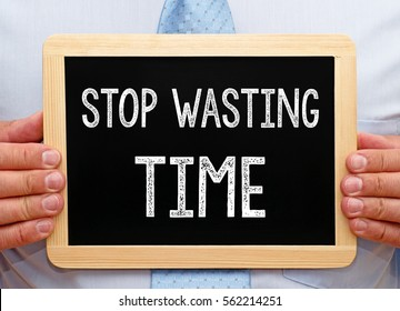 Stop wasting Time - Businessman holding chalkboard with text