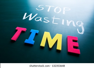 Stop wasting time concept, colorful words on blackboard
