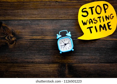 Stop wasting time hand letterng in cloud near alarm clock on dark wooden background top view space for text. Business concept, motivation