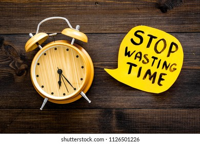 Stop wasting time hand letterng in cloud near alarm clock on dark wooden background top view. Business concept, motivation