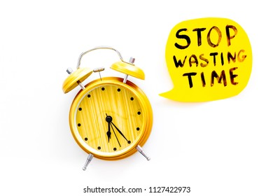 Stop wasting time hand letterng near alarm clock on white background top view copy space. Business concept, motivation