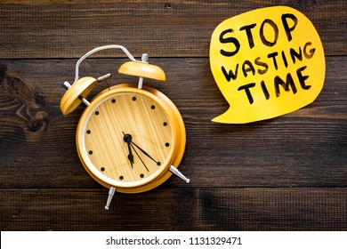 Stop wasting time hand letterng in cloud near alarm clock on dark wooden background top view copy space. Business concept, motivation