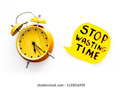 Stop wasting time hand letterng near alarm clock on white background top view. Business concept, motivation