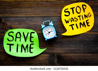 Stop wasting time, save time hand letterng in cloud near alarm clock on dark wooden background top view copy space. Business concept, motivation