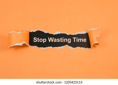 Stop Wasting Time text on paper. Word Stop Wasting Time on torn paper. Concept Image.