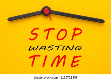 Stop wasting time written on yellow clock. Inspirational message.