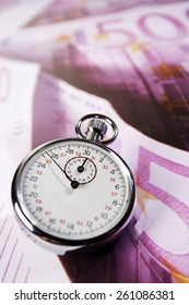 Stop watch and 500 Euro notes, time is money