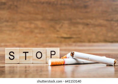 STOP word and tobacco on wooden background. World No Tobacco Day