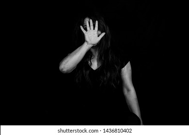 Stopping violence against women, Woman covering her face in fear of domestic violence, Dark tone