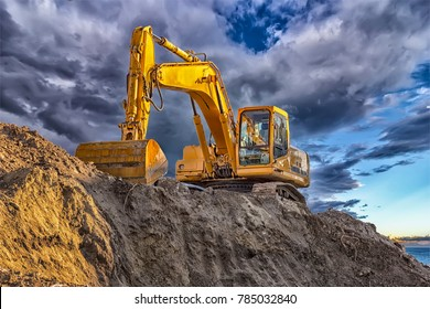 A stopping yellow excavator at an incredibly beautiful sunset