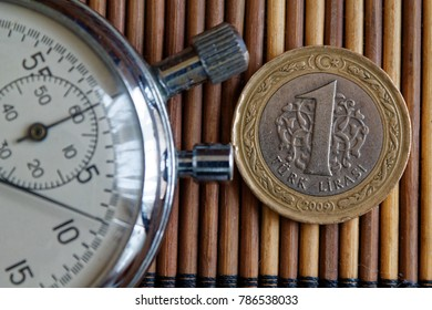 Stopwatch and coin with a denomination of one turkish lira on wooden table background