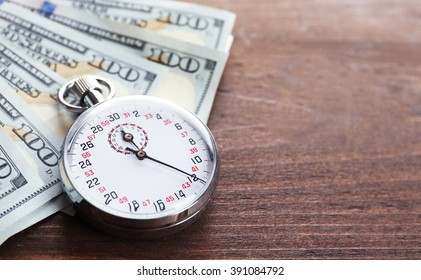 Stopwatch with dollar banknotes on wooden background. Time is money concept