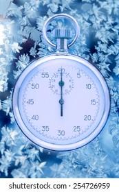Stopwatch on winter window ice frozen background