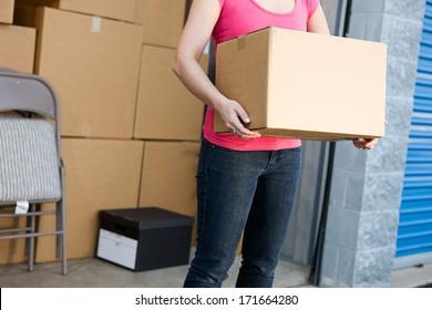 Storage: Anonymous Woman Holding Box By Storage Unit